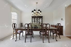 traditional formal dining room with white carpeting stock photo