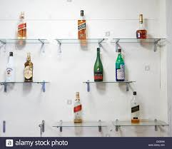 Shelves On Wall by Various Bottles Of Alcohol On Glass Shelves On A Wall Stock Photo