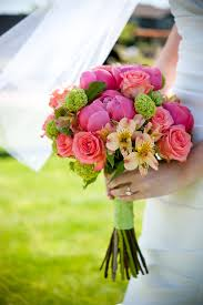 wedding flowers hull holding a pink coral light yellow and light green