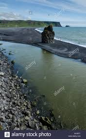 beaches with black sand rocks formation on dyrholaey cape with black sand beach and