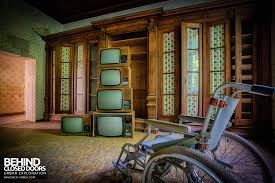 a wheel chair in front of a pile of old tvs in an abandoned