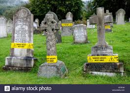 cemetery headstones unsafe headstones with yellow warning notices at a cemetery in