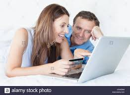 couple shopping online on bed stock photo royalty free image