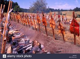 Cooking Over Fire Pit Grill - fish or vegetables are cooked outside over a fire stock photos