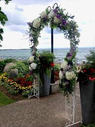 wedding arch of fresh hydrangeas purple roses wisteria and ruskus