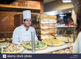 chef pizza chef in bakery serving pizza to client stock photo