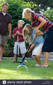 family playing croquet in the backyard stock photo royalty free