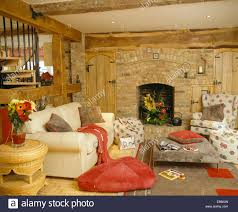 red floor cushion beside cream sofa in country living room with