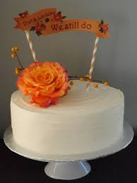red velvet anniversary cake with orange and burgundy rose hand