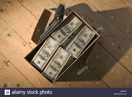 shoe box of dollar bills with gun on wooden floor stock photo