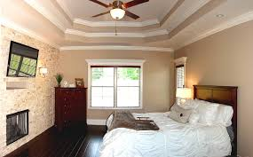 this master bedroom features a stone accent wall with fireplace