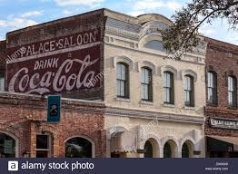 hand painted coca cola sign on exterior brick wall of old building