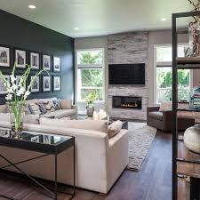 the dark accent wall fireplace and custom wood floors add warmth