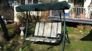 small stripped two seat patio swing with canopy two tones terrace