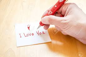 paper writing tablet hand holding red pen with white heart pattern writing i love hand holding red pen with white heart pattern writing i love you on note paper