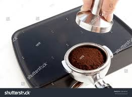 espresso ground coffee barista tamping coffee ground on rubber stock photo 558048505