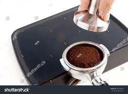 espresso ground coffee barista tamping coffee ground on rubber stock photo 558048505