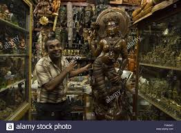 God Statue by Portrait Of Man Standing Near Hindu God Statue In Shop Colombo