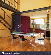 black chairs and glass table in large double height yellow hall