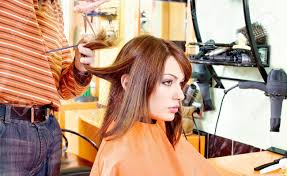 pretty woman and hands of hairdresser in hair salon cutting