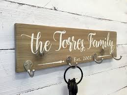 this personalized wooden key holder sign features zinc hooks for