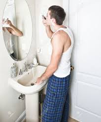 young man in bathroom looking in the mirror and shaving vertical