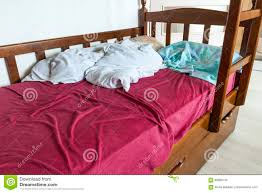 unmade child bed with crumpled red and white bed linens and pill