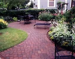 brick patio with flower bed and furniture create a fresh