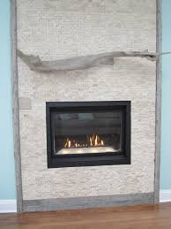 grey stone fireplace having carved grey wooden fireplace mantels