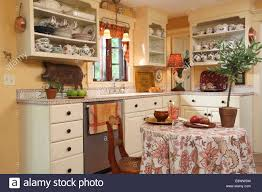 country style kitchen with open shelving and tile countertop in