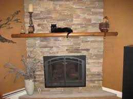 beige stone fireplace mantel with brown wooden shelf and black