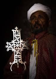 orthodox priest holding a cross inside a rock church