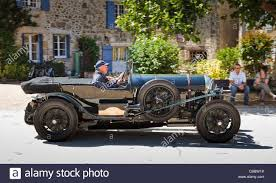 vintage bentley coupe classic car vintage bentley car driving through a village in the