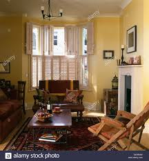 small brown leather sofa below window with plantation shutters in