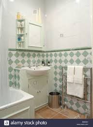 green and white tiles below dado in modern white bathroom with