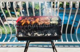 photo delicious meat on barbecue grill with coal on balcony