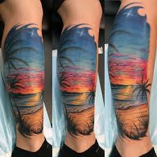 man with traditional beach and sunset tattoo on calf tattoo