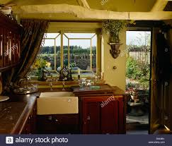 old fashioned belfast sink beneath window in country style kitchen