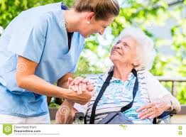 Home Nurse by Nurse Holding Hand Of Senior Woman In Pension Home Stock Photo