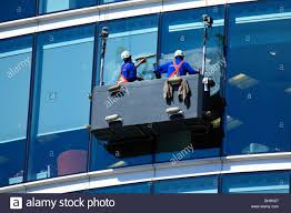 window cleaners suspended in a cradle washing glass curtain walls