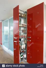 red modern kitchen pull out storage shelves in red larder cupboard in modern kitchen