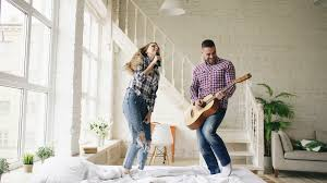 mixed race young funny girls dancing singing and playing acoustic funny happy and loving couple dance on bed singing with tv controller and playing guitar
