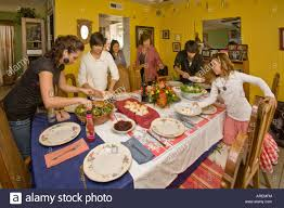 members of an extended hispasnic caucasian family prepare the