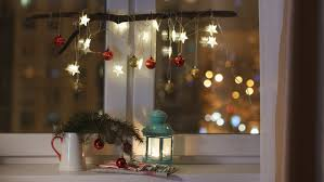 lantern with candle on a window sill with lights stock