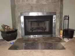 black metal fireplace with stainless around and silver hearth of