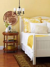 yellow bedroom ideas with lower chandelier and nightstand and
