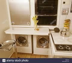 lave linge dans la cuisine four mural au dessus du lave linge et sèche linge dans la