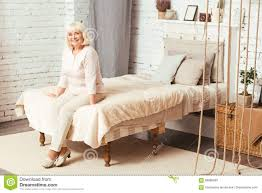 happy aged pensioner sitting in the bedroom stock photo image