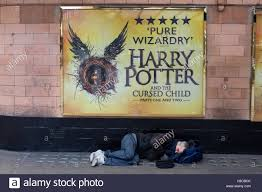 harry potter at the palace theatre on cambridge circus in london homeless man sleeps under the harry potter advertisement palace theatre soho