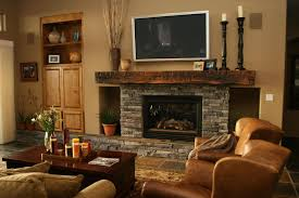 grey stone fireplace with dark brown wooden mantel shelf connected